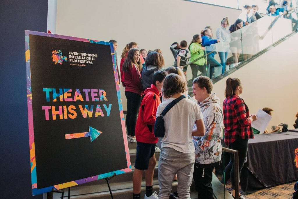 "Photo of people lined up at a film screening from 2019 and a sign that says ""Theater this way."""