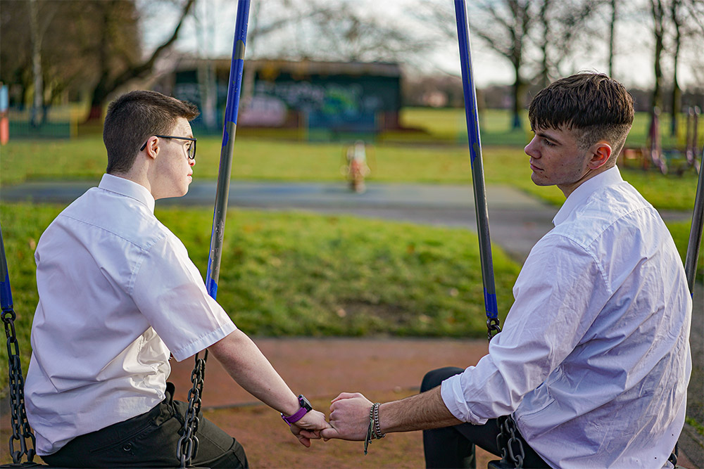 Two young men sit on swings outside holding hands.
