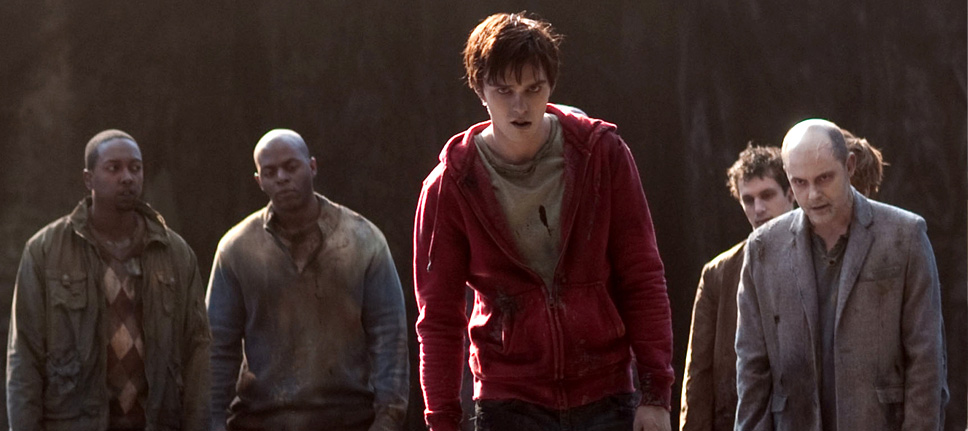 """The main character in """"Warm Bodies,"""" R, and other zombies stand hunched over looking at the camera."""